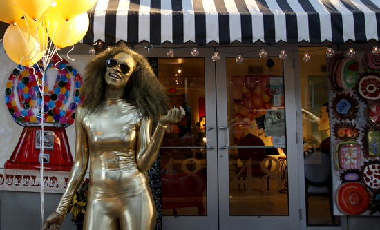 Painted gold, Nadiyah Skyy stands in front of Longshore Studio Gallery at Art for Arts' Sake in 2010. (UptownMessenger.com file photo by Sabree Hill)