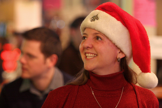 Kara Morgan, President of the Irish Channel, smiles while wearing a Saints-emblazoned Saints hat at the Irish Channel Neighborhood Association Christmas party at Tracey's bar in 2010, which included a toy drive in partnership with the New Orleans Police Department's Sixth District. (UptownMessenger.com file photo by Sabree Hill)
