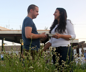 "Natalie Praetorius and Travis Brannen stand behind and arugula plant at Edible Schoolyard NOLA-An Edible Evening 2010 at the Samuel J. Green Charter School. Proceeds from the event go directly towards  program support to ensure the sustainability of the Edible Schoolyard NOLA's garden and kitchen programs.  ""We came here to see the garden and to eat,"" said Praetorius. (Sabree Hill, UptownMessenger.com)"