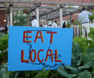 "A sign reading ""Eat Local""  in the edible garden at Samuel J. Green Charter School. (Sabree Hill, UptownMessenger.com)"