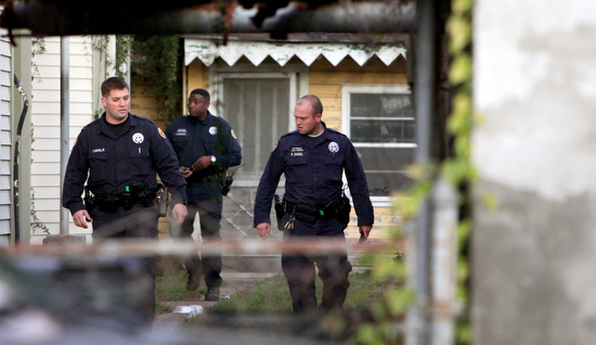 Members of the NOPD Sixth District task force search for an armed robbery suspect on Peniston Street in January 2012. The number of task force officers assigned to individual districts has dramatically decreased since then. (UptownMessenger.com file photo by Sabree Hill)