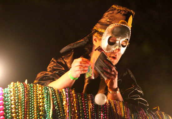 A  Krewe of Morpheus parader passes out throws from the top of a float. (Sabree Hill, UptownMessenger.com)