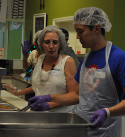 Volunteers Noel Bitner and Dat Nguyen serve Christmas dinner at the Bridge House/Grace House annual event in 2012. (UptownMessenger.com file photo by Marta Jewson)