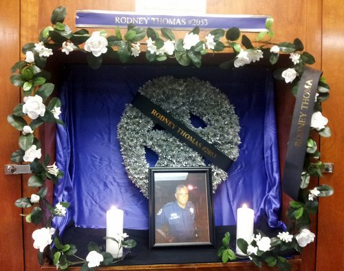 The memorial to Officer Rodney Thomas in the Second District roll call room, where officers gather before each shift. (Robert Morris, UptownMessenger.com)
