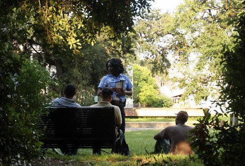 Detective Claudia Bruce hands out CrimeStoppers flyers to a group of men sitting in Coliseum Square during an anti-crime march in July 2013.  (UptownMessenger.com file photo by Robert Morris)