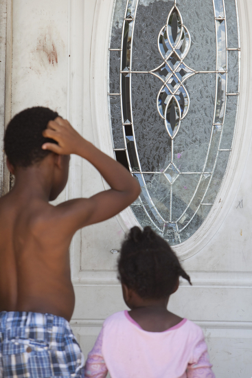 Children look at broken glass on the front door of the home where a shooting claimed the life of an eleven year old girl. (Sabree Hill, UptownMessenger.com)
