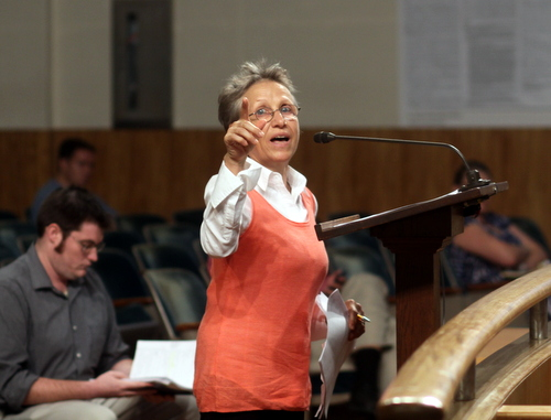 "Sylvi Beaumont, owner of the proposed ""Engine 37"" coffee house in the former Laurel Street fire station, points to a photo of the building as she addresses the City Planning Commission on Tuesday. (Robert Morris, UptownMessenger.com)"