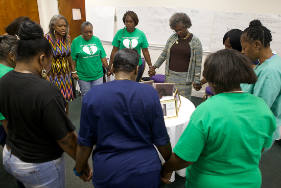 "The members of ""Helping Mothers Heal"" gather in a prayer circle at one of their weekly meetings on September 26, 2013. Helping Mothers Heal is a group of mothers who have lost a child to violence. (Sabree Hill, UptownMessenger.com)"