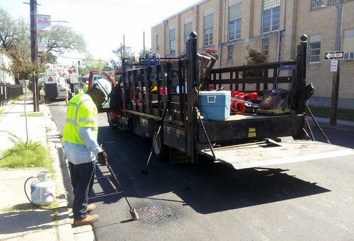 A construction worker touches up the area around a drain cover on a newly repaved section of Freret Street on Friday afternoon. (Robert Morris, UptownMessenger.com)
