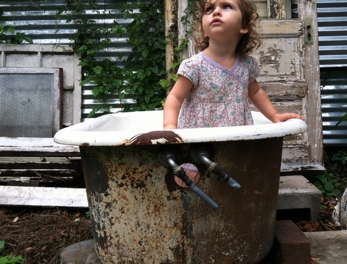 From December 2012, the youngest Villere daughter pauses at play inside a backyard clawfoot tub. (by Jean-Paul Villere for UptownMessenger.com)