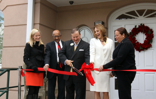 Poydras Home CEO Jay Rive cuts the ribbon at the entrance of the new Oak House building, surrounded by (from left) Lauren Hotard of Councilwoman Stacy Head's office, chaplain Roosevelt Stephens, board president Jill Winston and City Councilwoman Cynthia Hedge-Morrell. (Robert Morris, UptownMessenger.com)