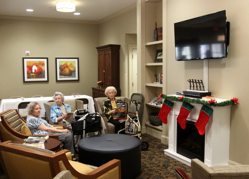 Poydras Home residents relax in a living room area of the new Oak House building after the opening ceremony. (Robert Morris, UptownMessenger.com)