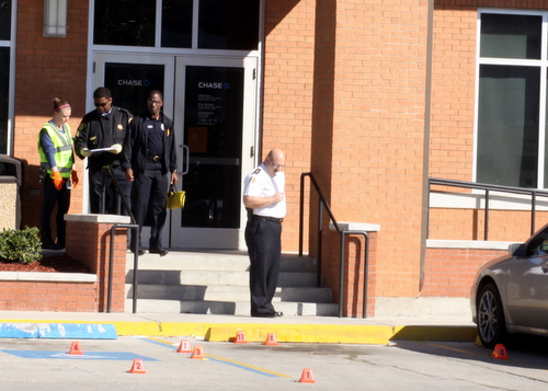 Investigators place evidence cones in the parking lot of the Chase bank at Carrollton and Claiborne after an armored-car guard was fatally shot Wednesday morning. (Robert Morris, UptownMessenger.com)