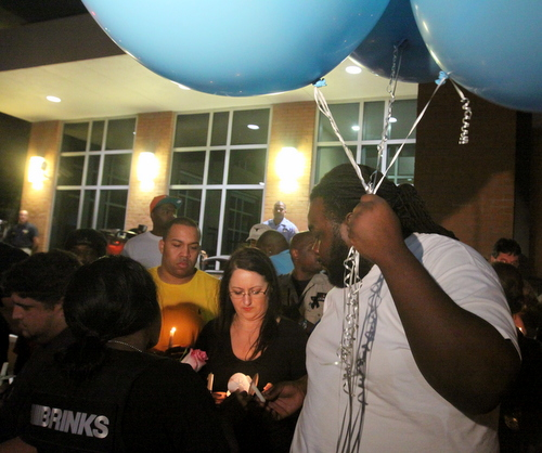 "Justin Rivers carries large blue balloons that read, ""RIP Hector."" (Robert Morris, UptownMessenger.com)"