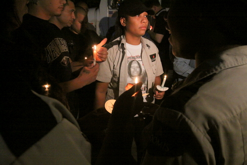 Loomis employees light one another's candles at the vigil. (Robert Morris, UptownMessenger.com)