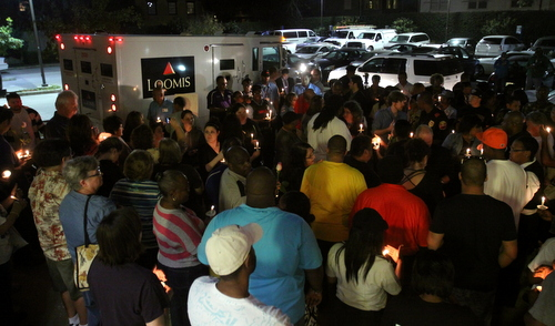 Mourners gather between two Loomis trucks at the vigil. (Robert Morris, UptownMessenger.com)