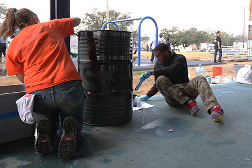 Kayla Macgregor (left) and D'Andre Williams (right) repaint a trashcan by the basketball court in A.L. Davis Park. Macgregor, a Boston native, is in New Orleans with Americorps. (photo by Zach Brien for UptownMessenger.com)