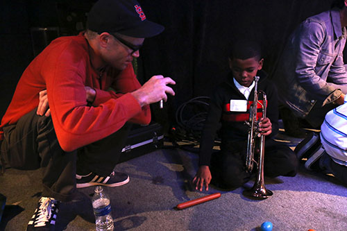 Little Big Horns' Trombonist Charlie Halloran (left) puts down his bone to give percussion instruction to Jacob Jones (right).