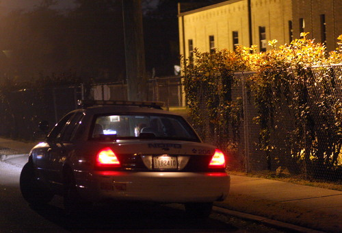 A police officer parked on Willow Street near Nashville works on a report following a robbery call Sunday evening. (Robert Morris, UptownMessenger.com)