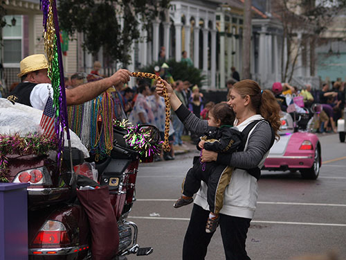 Young parade goer receives a plush toy from a Gold Wing Road Rider. Krewe of Carrollton 2014. (Zach Brien, UptownMessenger.com)