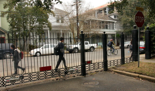Pedestrians pass by the Newcomb Boulevard fence in early February. (UptownMessenger.com file photo)