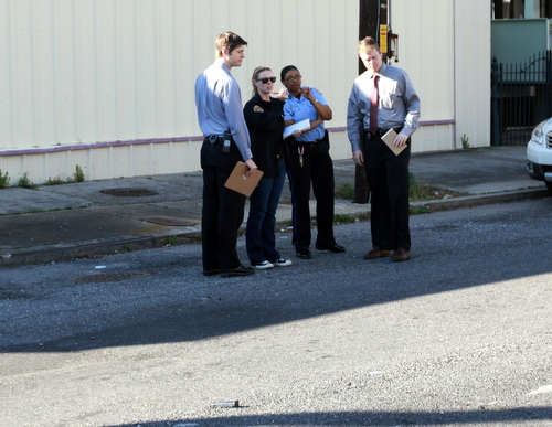 NOPD investigators confer near a gun magazine and shell casings found at the scene of a shooting on O.C. Haley Boulevard on Tuesday. (Robert Morris, UptownMessenger.com)