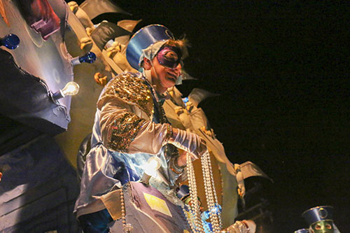 "Rider from the ""Deep Sea Fishing in the Gulf"" float prepares to throw beads to the crowd."