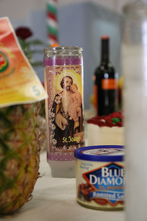 St. Joseph candle among food offerings at De La Salle's St. Joseph altar. (Zach Brien, UptownMessenger.com)