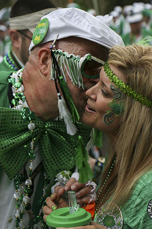 Dana Prados (right), receives a kiss on the cheek in exchange for a flower during Saturday's Irish Channel Parade.