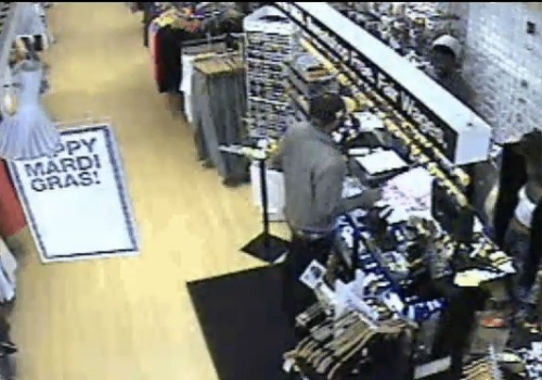 The suspected robber holds a gun at the counter of American Apparel (NOPD)