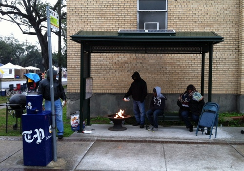 Revelers awaiting Rex on Mardi Gras Day underneath the bus stop at Freret and Napoleon fuel their fire in an effort to keep warm. (Photo by Jean-Paul Villere for UptownMessenger.com)
