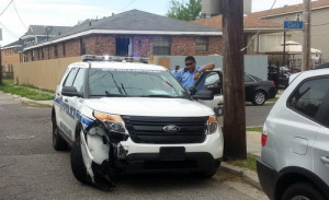An officer inspects damage to a police SUV on Clara Street following the pursuit. (Robert Morris, UptownMessenger.com)