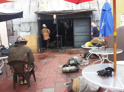 Firefighters cool down on the back patio of the Rendon Inn after extinguishing the blaze inside Hangar 13 next door. (Robert Morris, UptownMessenger.com)