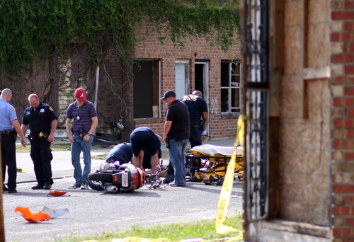 Paramedics tend to a motorcyclist injured near a shooting scene on Fourth Street in Central City. (Robert Morris, UptownMessenger.com)