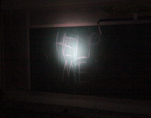 "Light from a flashlight illuminates the message ""Help me"" scrawled on a chalkboard inside a darkened Priestley classroom. (Robert Morris, UptownMessenger.com)"