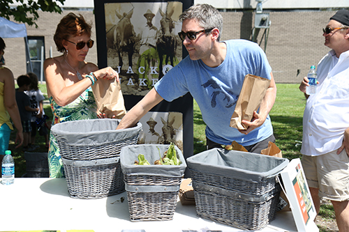 Jennifer Burg (left) and Daniel Momont (right) of Jack and Jake's organic food market pack bags of fresh produce. (Zach Brien, UptownMessenger.com)