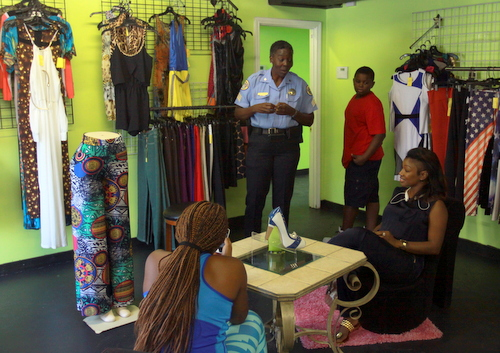 NOPD Sgt. Yolanda Jenkins speaks to citizens inside the clothing shop adjacent to the damaged salon. (Robert Morris, UptownMessenger.com)