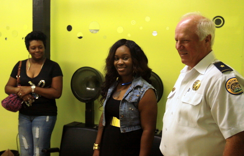 NOPD Commander Bob Bardy speaks to salon owner Creaster Pinkney (center) and one of her stylists Tuesday after the department boarded the building up. (Robert Morris, UptownMessenger.com)