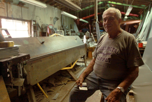 Raymond Twickler Jr. holds an order pad in his metal shop on Cadiz Street.  (Robert Morris, UptownMessenger.com)