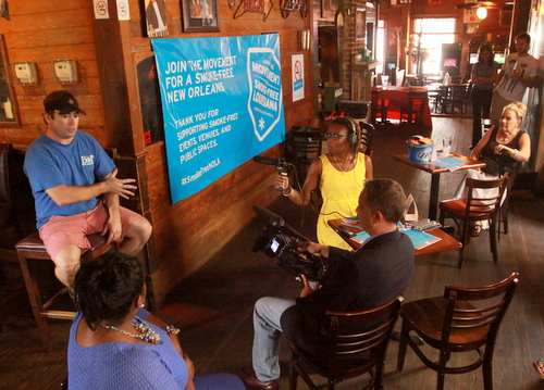 Carrollton Station owner Michael Miller (left) explains his experience taking his bar smoke-free to a handful of non-smoking advocates, members of the media and smoker Elizabeth Stella (seated far right) on Wednesday afternoon. (Robert Morris, UptownMessenger.com)