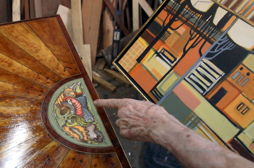 Ruppert Kohlmaier, a well-known New Orleans woodworker, gestures to the inlay he is designing on a custom chest of drawers in his shop next to the controversial green space. (Robert Morris, UptownMessenger.com)