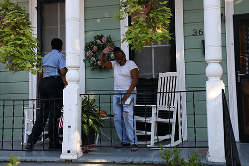 Officer Erica Whitley delivers a crime stoppers pamphlet to Ella Adams Gaynor on the porch of her mother's home on Laurel street. (Zach Brien, UptownMessenger.com)