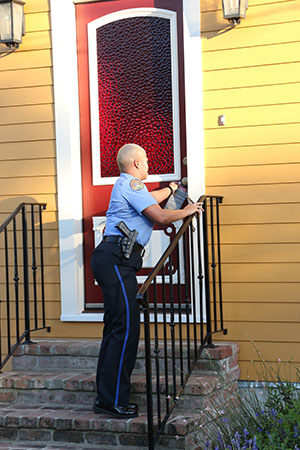 Officer Anya Hilliard leaves a crime stopper pamphlet at a home on Constance street. Hilliard has been serving the sixth district for five and a half years. Because she grew up there, Hilliard says she takes her job personally. (Zach Brien, UptownMessenger.com)