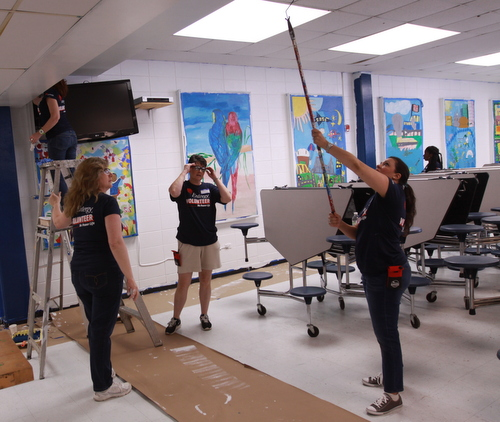 Volunteers paint the Benjamin Banneker cafeteria walls around murals left from the former school. (Robert Morris, UptownMessenger.com)