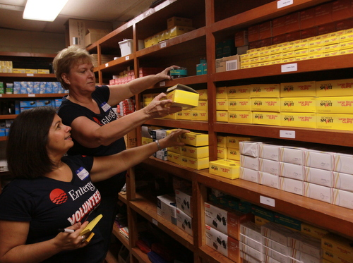 Volunteers stock shelves with school supplies at the Benjamin Banneker campus. (Robert Morris, UptownMessenger.com)