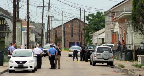 Crime-scene technicians photograph evidence marked by yellow cones in the road and on the sidewalk after a shooting Wednesday afternoon at the intersection of St. Andrews and South Liberty streets in Central City. (Robert Morris, UptownMessenger.com)