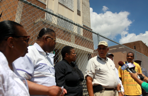 Retired Lt. Gen. Russell Honore (center) and other advocates discuss contamination in the soil at the former Booker T. Washington site in front of what remains of the former school in September 2014. (Robert Morris, UptownMessenger.com)