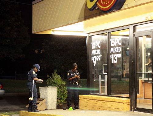 Crime-scene investigators examine evidence cones on the sidewalk next to Church's Chicken on Sunday evening. (Robert Morris, UptownMessenger.com)
