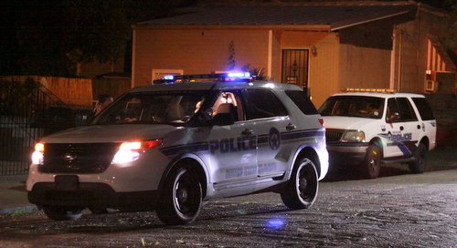Two police officers parked on Eighth Street confer during a home-invasion investigation Friday. (Robert Morris, UptownMessenger.com)