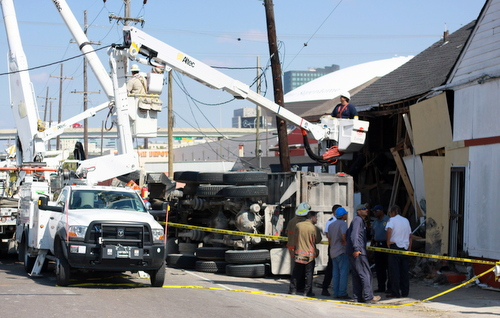 Workers try to clear an overturned dump truck that crashed into a building on South Claiborne on Monday. (Robert Morris, UptownMessenger.com)